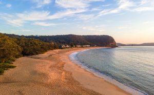 Calm seas aerial sunrise at Pearl Beach on the Central Coast, NSW, Australia.